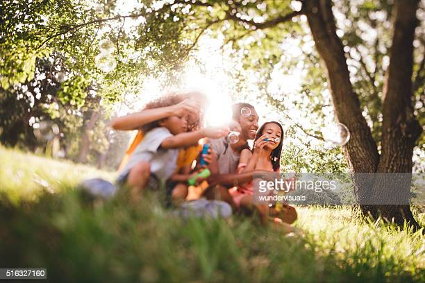 Young african-american family blowing bubbles and laughing toget