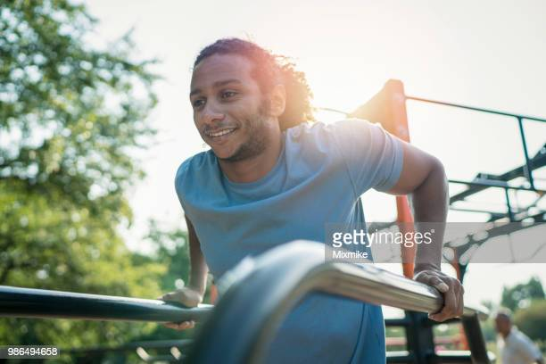 young african-american male training arm muscles in the park - exercise equipment stock photos and pictures