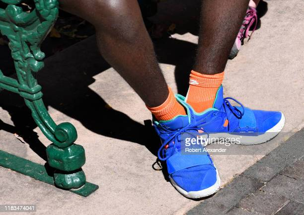 A young AfricanAmerican man wearing Nike Paul George basketball shoes sits on a park bench in Santa Fe New Mexico