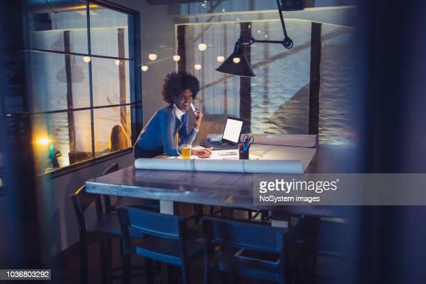 arquiteto de mulher jovem afro-americano trabalhando em um projeto. - só uma mulher jovem - fotografias e filmes do acervo