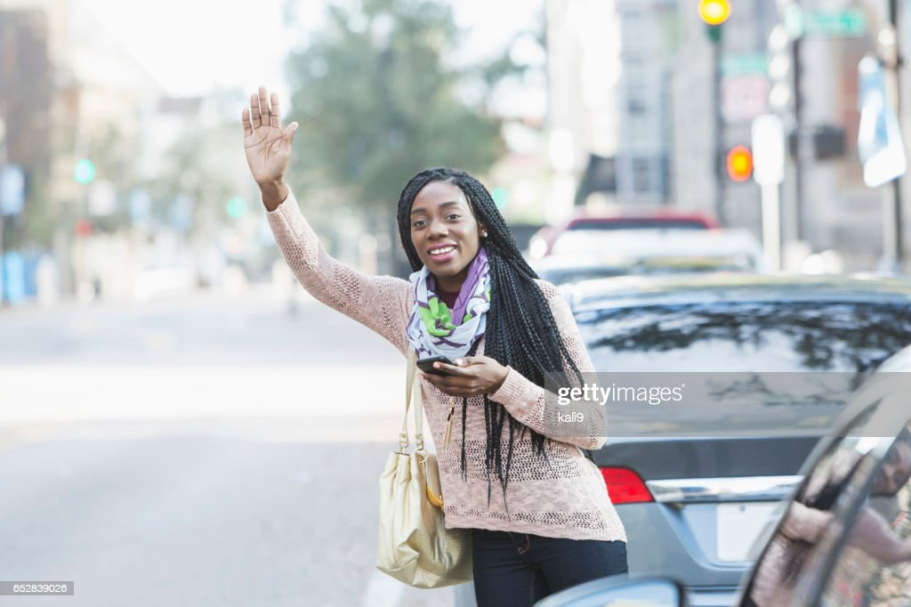 Young African-American woman in city looking for her ride : Stock Photo