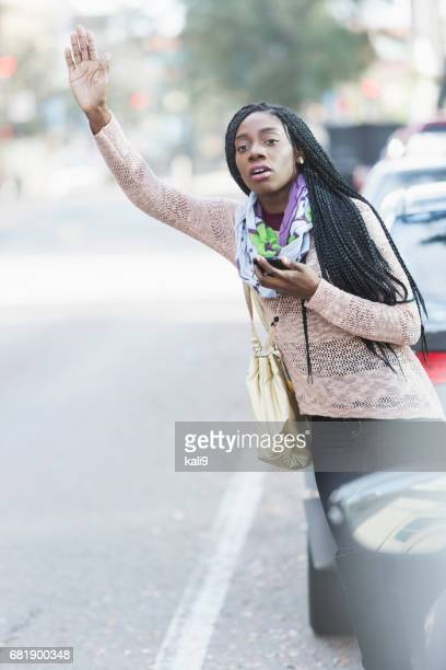 Young African-American woman in city looking for her ride