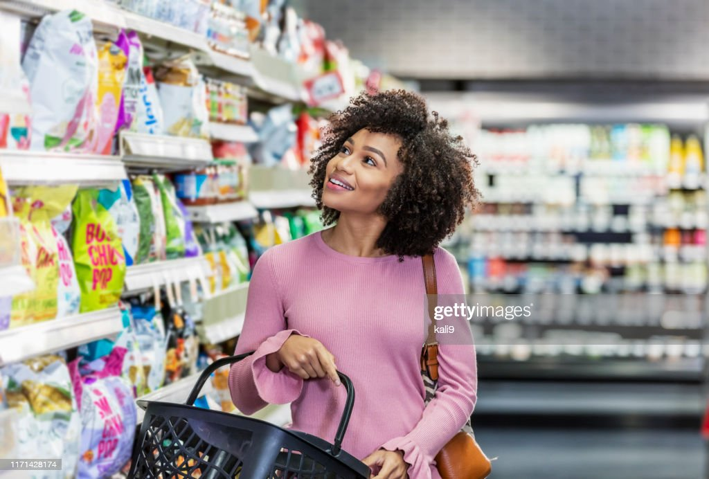 Young African-American woman shopping in supermarket : Stock Photo