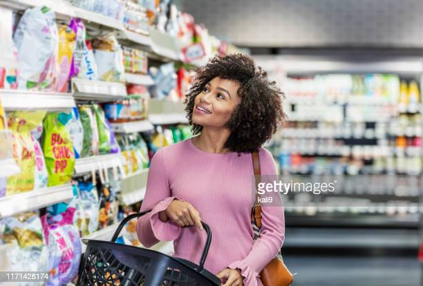 young african-american woman shopping in supermarket - groceries stock pictures, royalty-free photos & images