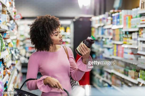 young african-american woman shopping in supermarket - market retail space stock pictures, royalty-free photos & images