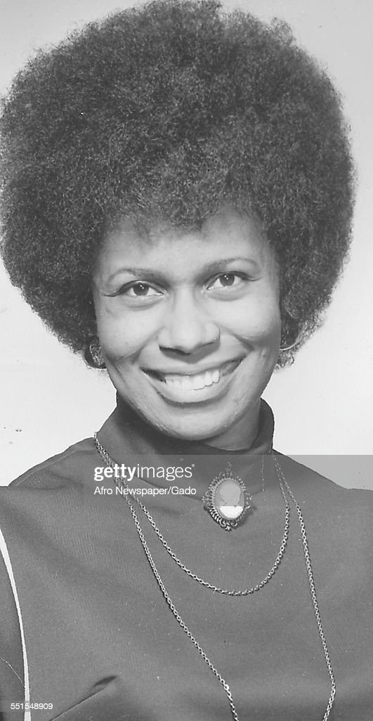 A young African-American woman smiling at the camera, with an Afro haircut and a high necked blouse, 1955.