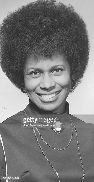 A young AfricanAmerican woman smiling at the camera with an Afro haircut and a high necked blouse 1955