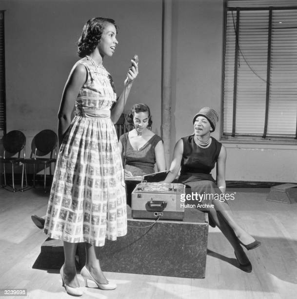 A young AfricanAmerican woman stands with a microphone speaking as two women sit with a reeltoreel tape recorder listening to her inside a studio...