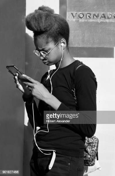 A young AfricanAmerican woman uses her smartphone while waiting for a shop to open on Fifth Avenue in New York City