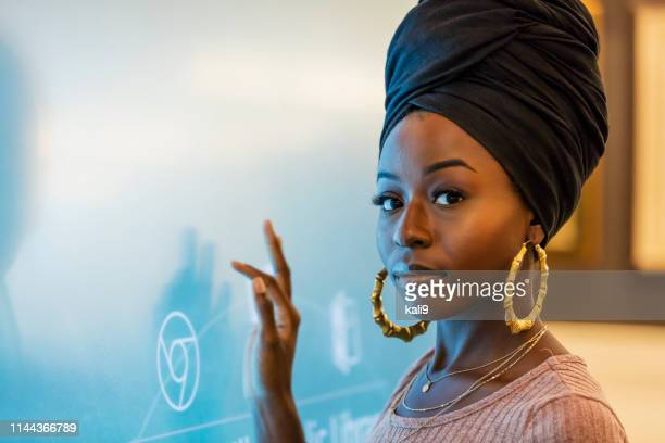 young african-american woman using interactive display - headscarf stock pictures, royalty-free photos & images