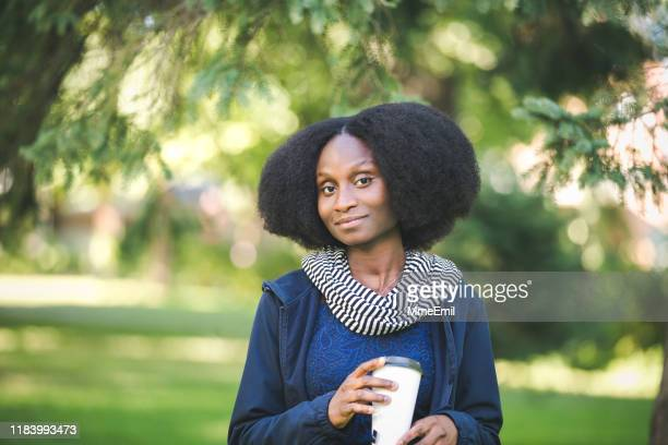 young african-american woman walking in a public park with a tea to-go - mmeemil stock photos and pictures