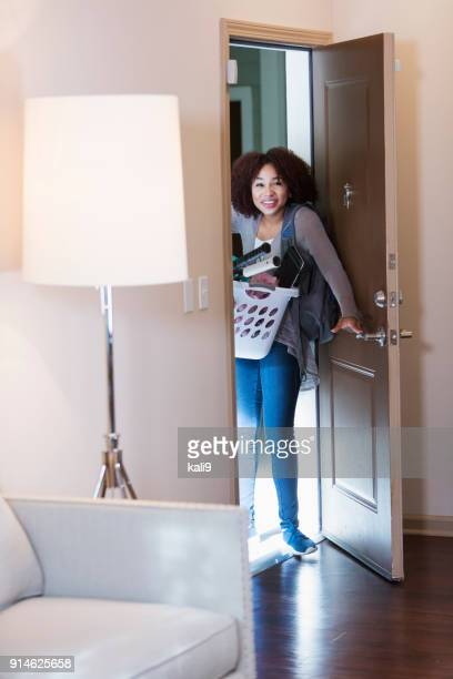 junge afroamerikanerin, die zu fuß durch tür - eintreten stock-fotos und bilder