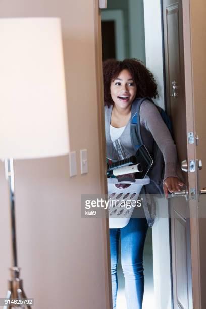 Mujer joven afroestadounidense caminando a través de la puerta