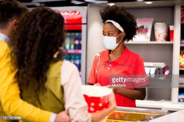 jonge afrikaans-amerikaanse vrouw die bij de bioskoopbar werkt - filmpremière stockfoto's en -beelden