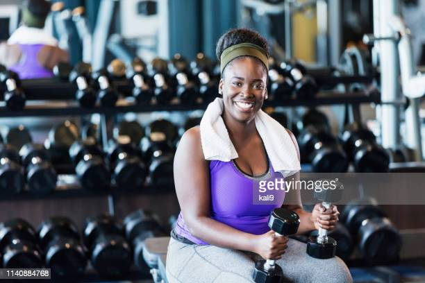 young african-american woman working out at the gym - curvy african women stock pictures, royalty-free photos & images