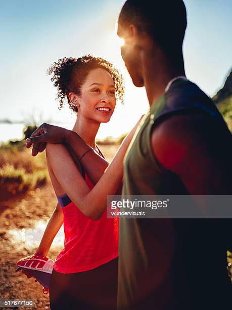 Young African-descent couple warming up before jogging outdoors