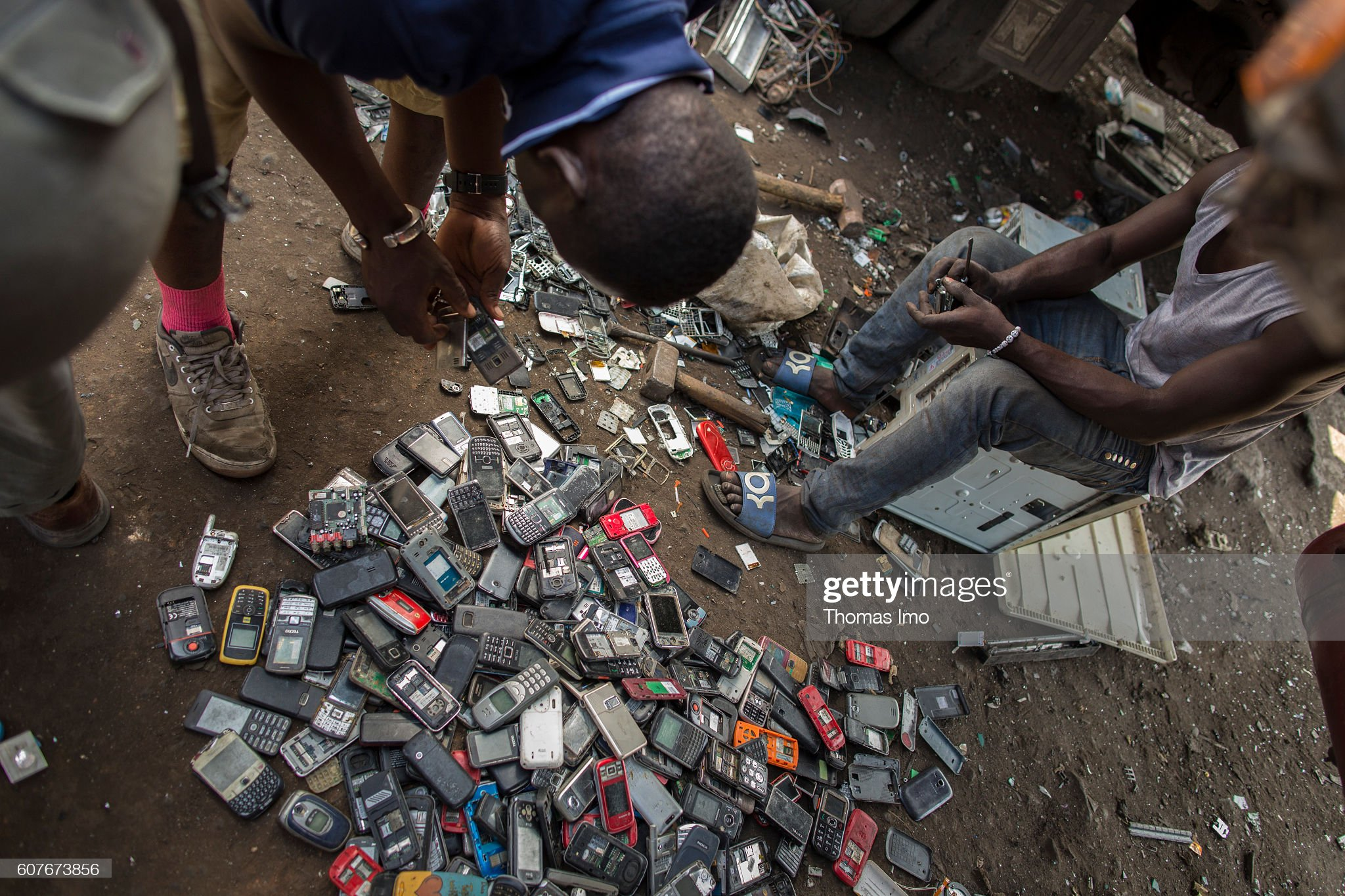 young-africans-disassemble-old-mobile-phones-on-the-largest-scrap-picture-id607673856