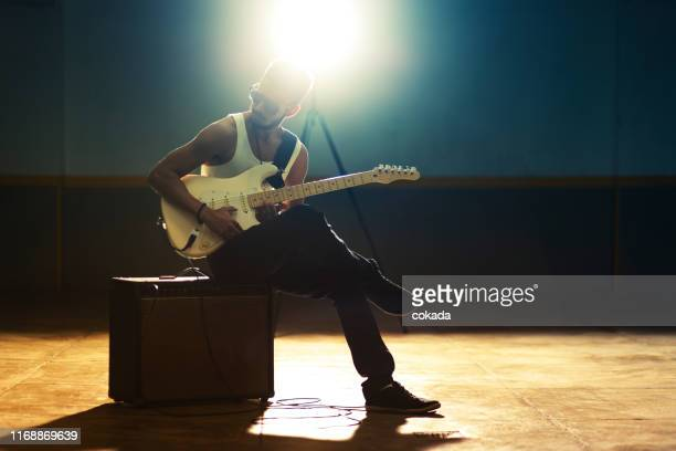 young afro american man playing electric guitar - guitarist stock pictures, royalty-free photos & images