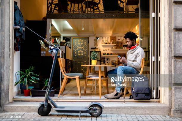 young afro american man sitting in a cafe - electric scooter stock pictures, royalty-free photos & images