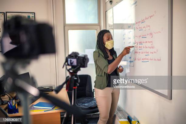 young afro american woman, female teacher standing near whiteboard - teacher stock pictures, royalty-free photos & images