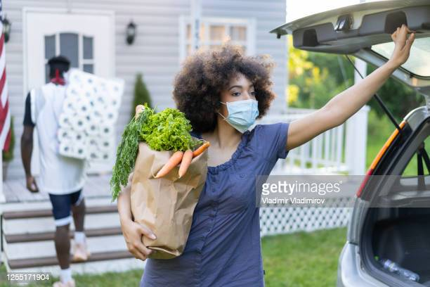 young afro couple unloading grocery bags and toilette paper after arriving from shopping at moment of virus pandemic - men wearing stockings stock pictures, royalty-free photos & images