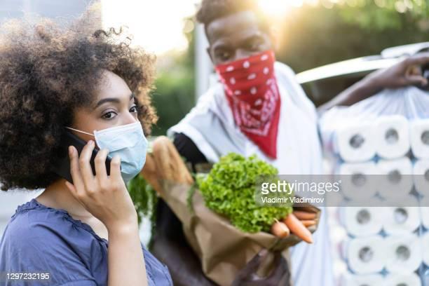 ウイルスパンデミックの瞬間に買い物から到着した後、食料品袋やトイレットペーパーをアンロードする若いアフロカップル - ゲートル ストックフォトと画像
