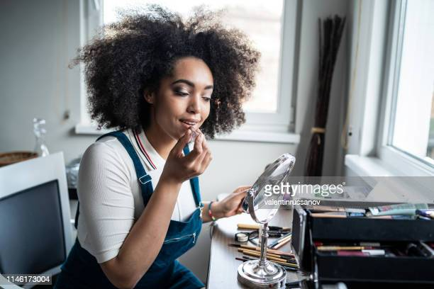 young afro woman applying lipstick at home - matte lips stock pictures, royalty-free photos & images