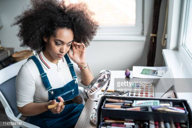 young afro woman applying makeup at home - matte lips stock pictures, royalty-free photos & images