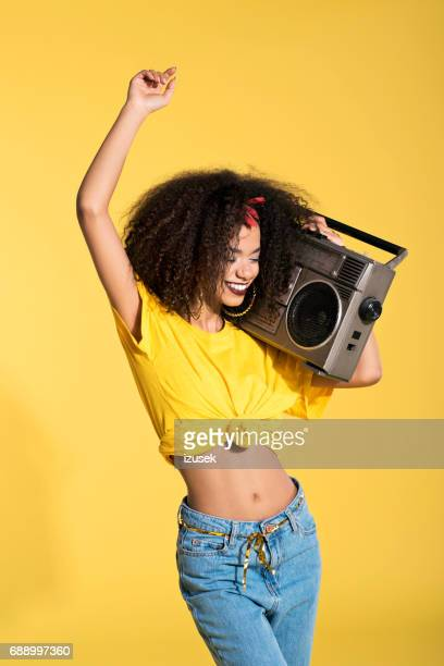Young afro woman holding boombox and dancing