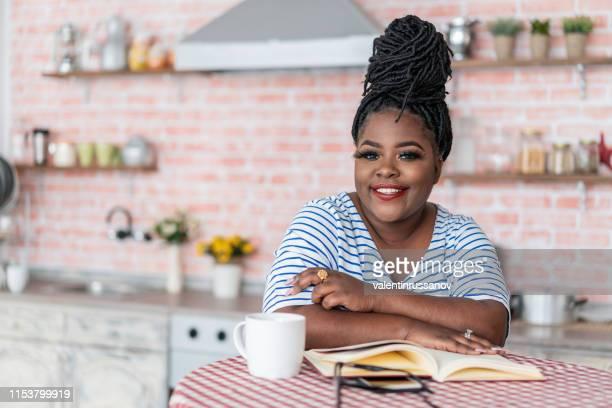 mulher afro nova que lê um livro em casa - literatura - fotografias e filmes do acervo