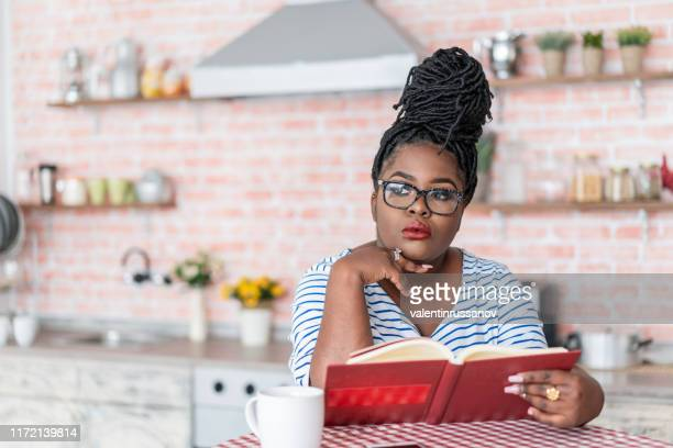 young afro woman reading a book at home - poet stock pictures, royalty-free photos & images