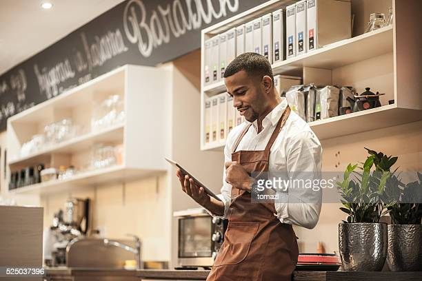 Young afro-american bar owner ordering stock