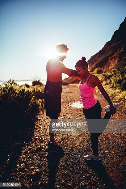 Young afro-american couple warming up before running outdoors