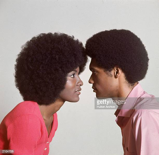 A young AfroAmerican couple with afro hairstyles stand face to face circa 1970