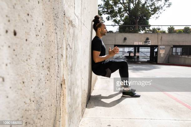 young afroamerican man getting fit in los angeles downtown city streets - sitting stock pictures, royalty-free photos & images