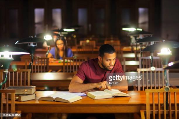 afroamerikanische jüngling studieren in der bibliothek - bibliothek stock-fotos und bilder