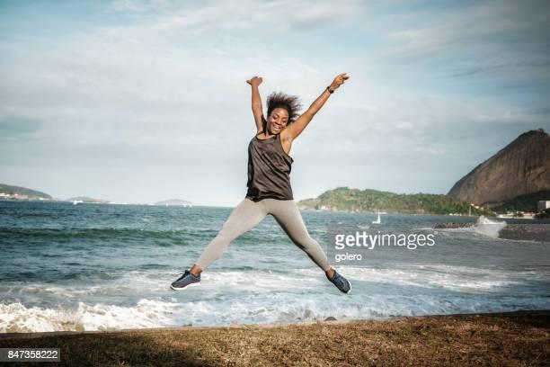 mujer afro brasileña joven saltando en la playa con pan de azúcar