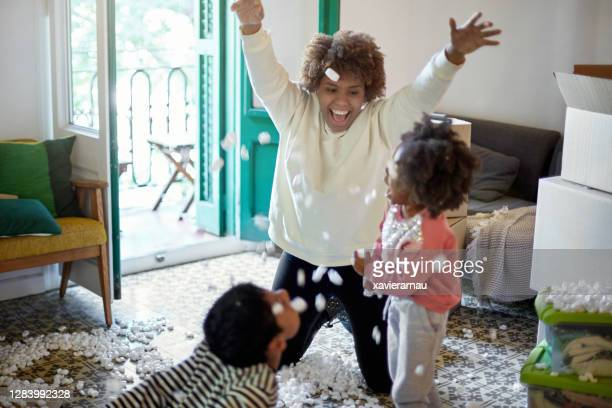 young afro-caribbean family playing with packing peanuts - afro caribbean ethnicity stock pictures, royalty-free photos & images