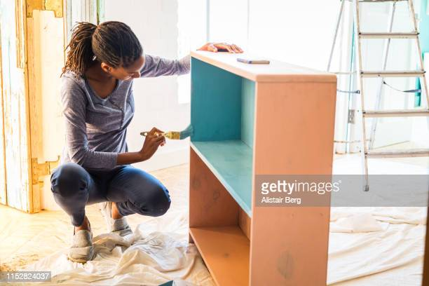 young afro-caribean woman renovating her home - home improvement stock pictures, royalty-free photos & images