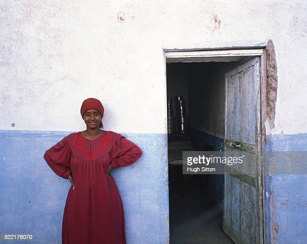 young agytian woman standing in front of a house - hugh sitton stock pictures, royalty-free photos & images