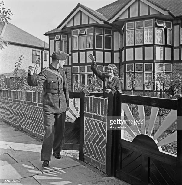 Young air cadet waves goodbye to his mother, standing at the front gate of the family house, as he leaves to take part in his first parade at an Air...