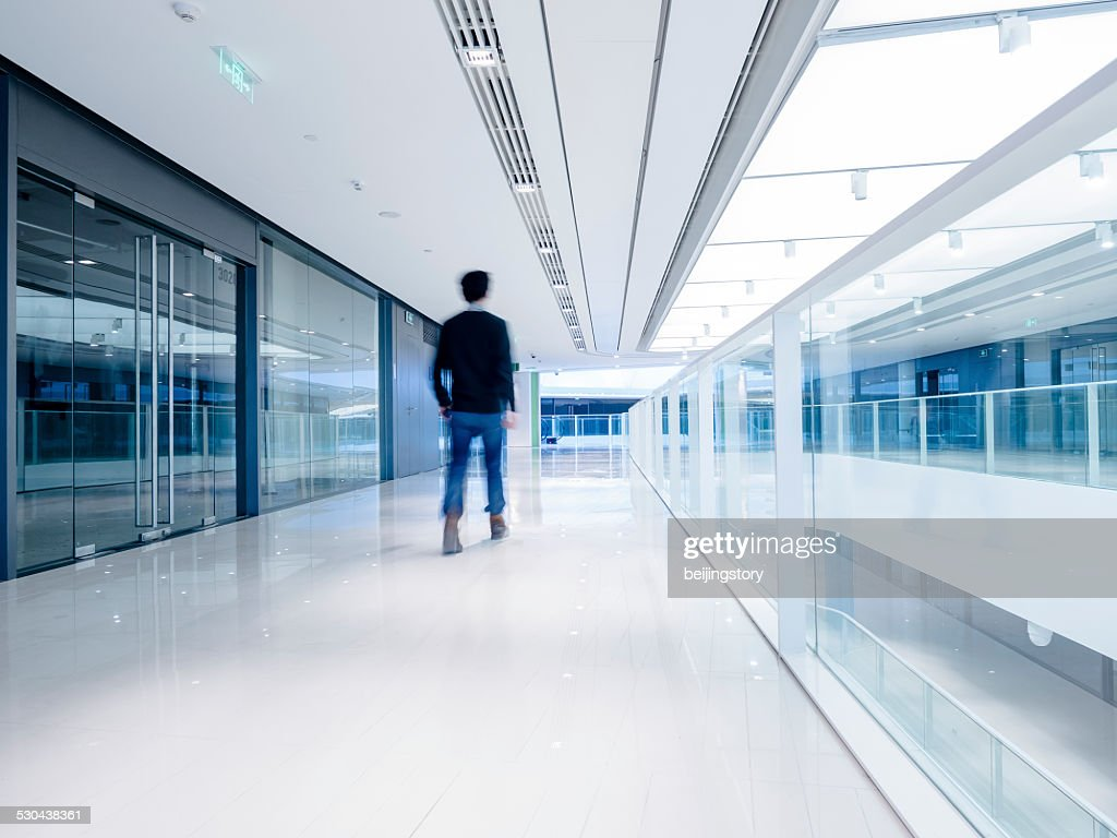 Young aisian businessman walking in architecture : Stock Photo