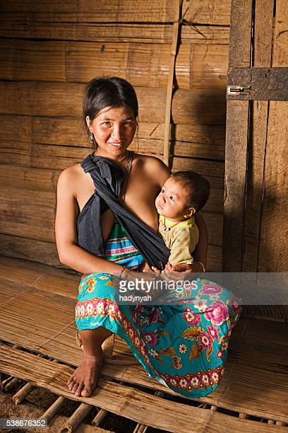 Young Akha mother holding her baby in Northern Laos