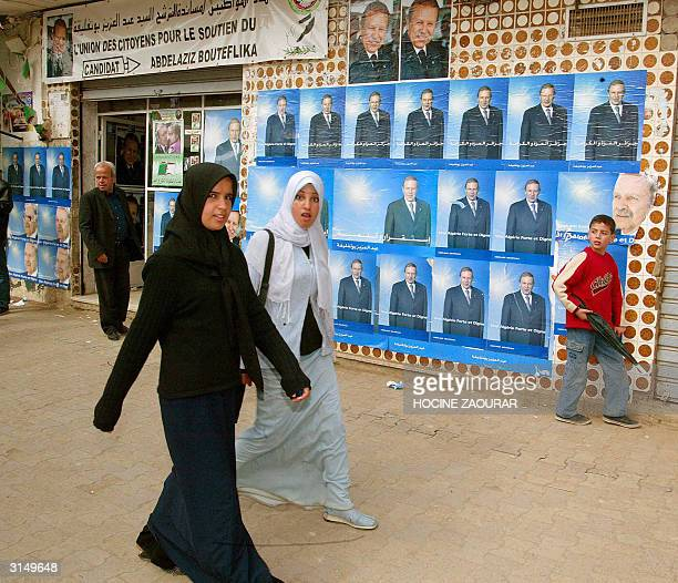 Young Algerian girls pass in front of a local party election office for President Abdelaziz Bouteflika 28 March 2004 in Algiers Presidential...