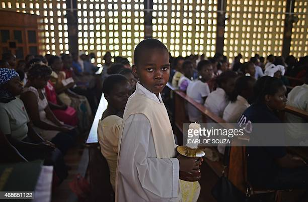 A young altar server holds a candle during a Easter service at the Catholic cathedral in Garissa on April 5 mourning the country's worst ever...