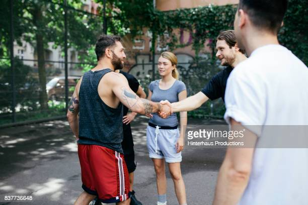 Young Amateur Athletes Shaking Hands Before Friendly Game Of Basketball Outdoors