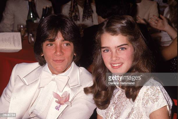 Young American actors Scott Baio and Brooke Shields smile while sitting together at an unidentified event circa 1978