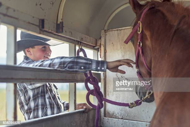 Young american boy preparing horse out of the trailer for an event