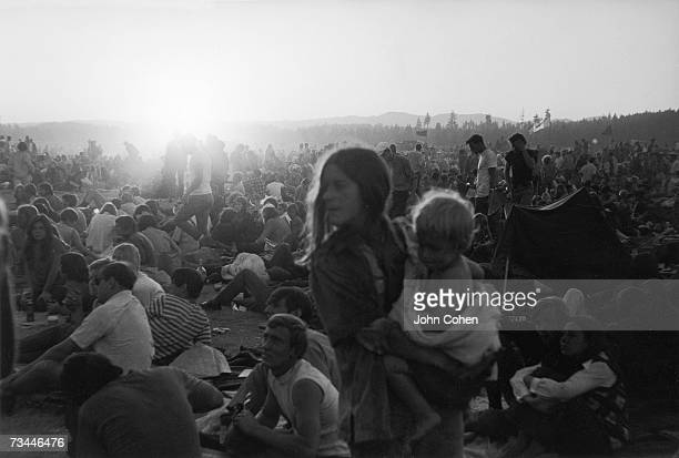 A young American hippie woman holds her baby in her arms amid the crowd at the second Sky River Rock Festival and Lighter Than Air Fair a rock music...