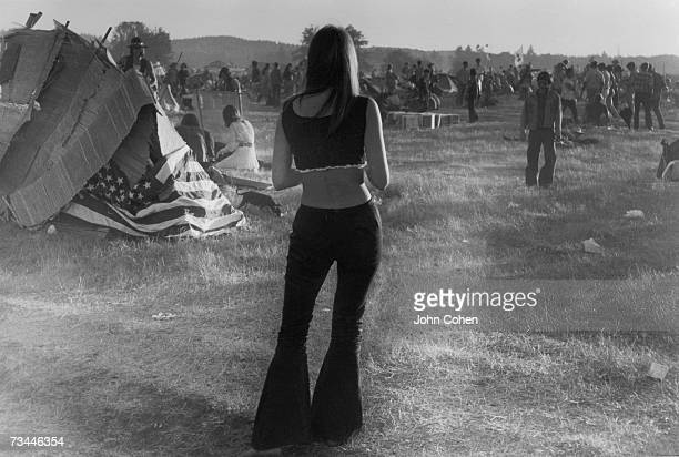 A young American hippie woman is seen from the back as she gazes out at a field of fellow festival goers in their encampment at the second Sky River...